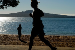 A walker and jogger enjoy the early morning winter sun, Cheltenham Beach, Devonport. Photo / Michael Craig
