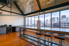 The interior of 23 Union St, Auckland, features industrial-style open-plan office space with expansive windows.