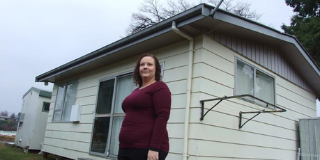 Alycia Burke stands in front of the cabin in which she and her young family live. It will be removed to make room for a 10-house development. Photo / Christina McDonald