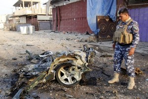 An Iraqi soldier inspects the wreck of a car bomb after it exploded in the military zone of the northern Iraqi city of Kirkuk.Photo / AFP