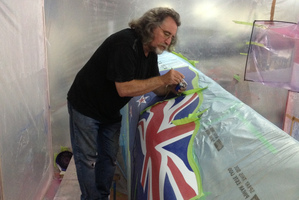 Rotorua airbrush artist Warren Houston paints the New Zealand flag onto the America's Cup catamaran