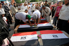 Supporters of ousted President Mohammed Morsi prepare symbolic coffins, representing some 51 people killed. Photo / AP