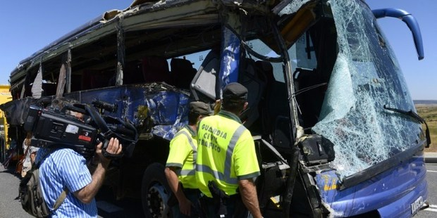Members of Spain's Guardia Civil inspect a damaged bus after it crashed on the N-403 road, near Avila, killing nine. Photo / AFP