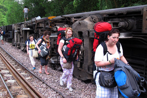 Passengers carry their belonging as they leave form a derailed train in Phrae province, northern Thailand. Photo / AP