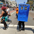 An attendee dressed as a police public call box crosses the street on Day 2. Photo / AP