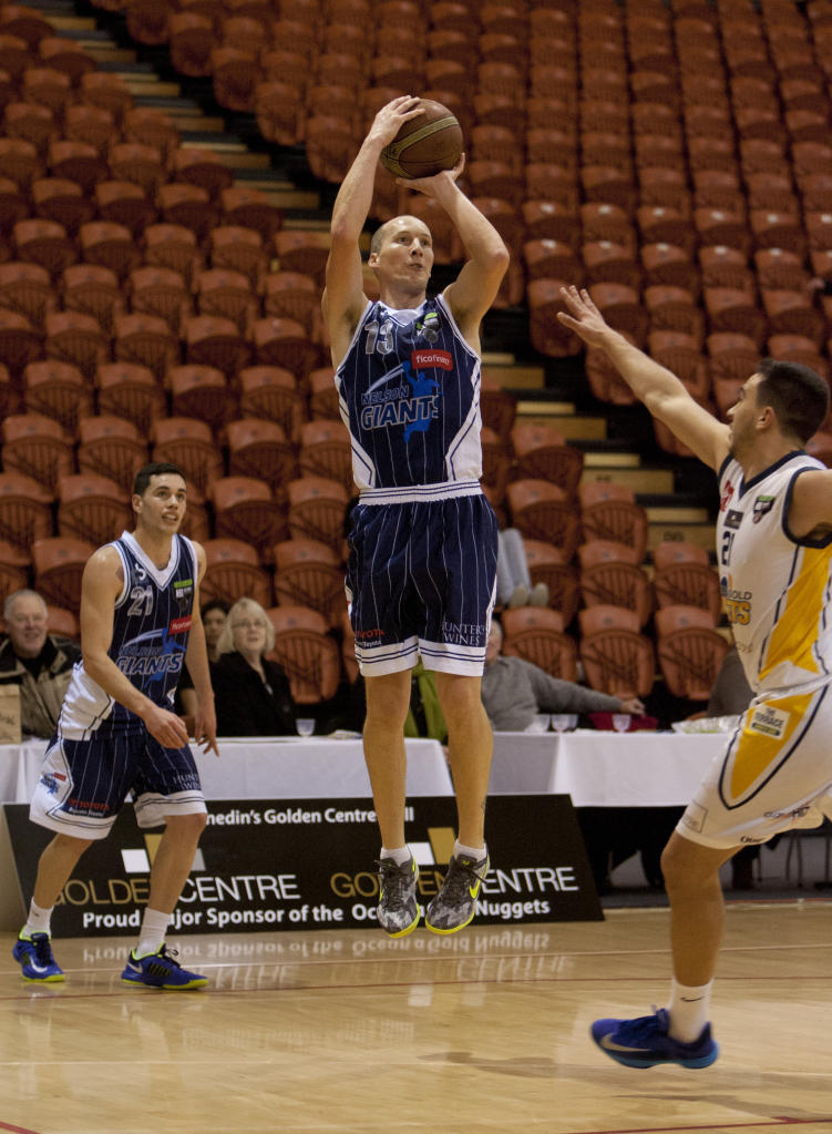 Josh Bloxham, Giants guard, watches Phill Jones, his veteran teammate, defy gravity as Otago player Riki Buckrell defends.