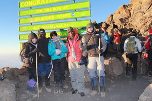 A congratulations sign greets me (right) at the top of Mt Kilimanjaro.