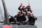 Emirates Team New Zealand crew wave to spectators after round-robin racing in their AC72 22m catamaran. Photo / Chris Cameron