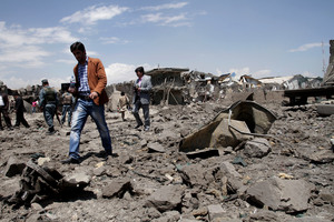 Afghan security personnel and media people walk around the site of a suicide car bombing. Photo / AP