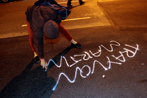 A woman spray paints along a street during a protest in Oakland after George Zimmerman was found not guilty. Photo / AP