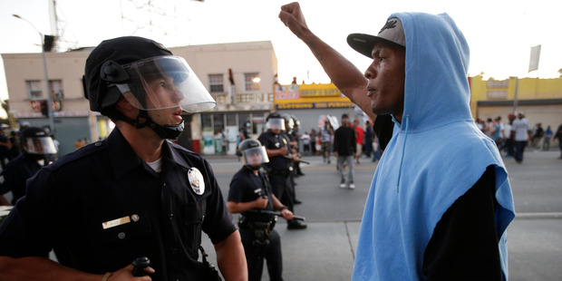 A protester confronts a Los Angles police officer during a demonstration in reaction to the acquittal of neighborhood watch volunteer George Zimmerman. Photo / AP