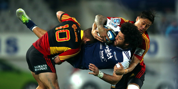 Rene Ranger of the Blues is dumped by Aaron Cruden (L) and Tim Nanai-Williams (R) of the Chiefs during the round 20 match between the Blues and the Chiefs at Eden Park. Photo / Getty Images.