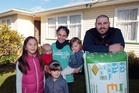 Mum Kate Parker with kids, and Sam Light from Right House Insulation at a Green Bay rental property. Photo / Doug Sherring