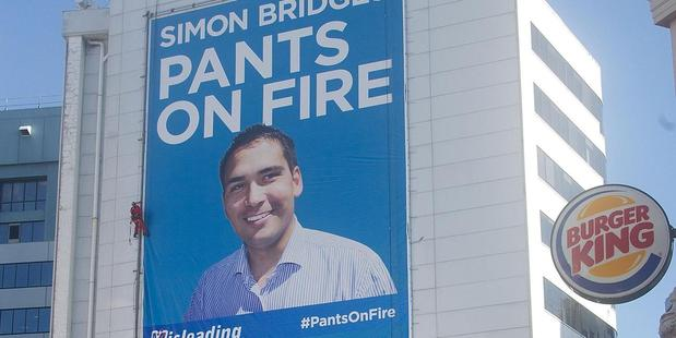 Abseilers install a billboard reading: Simon Bridges Pants on Fire'. Photo / supplied