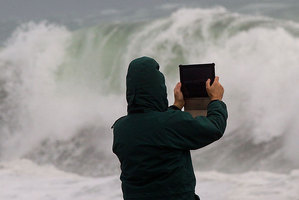 A man photographs the waves as the South coast of Wellington gets battered by high seas. Photo / Marty Melville