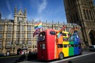 Gay campaigners drive a bus past the Houses of Parliament as the Marriage (Same Sex Couples) Bill gets an unopposed third reading by the Lords in central London. Photo / AFP