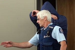 A police officer leads one of the accused into court during an earlier appearance.  Photo / Wairarapa Times-Age