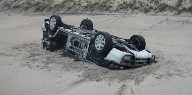 Police are stumped as to how this car ended up upside-down and buried on Tauranga Beach. Photo / Bay of Plenty Regional Council