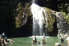 Children play in the water at the foot of the Kitekite Falls. Photo / Supplied