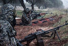 Syrian rebel fighters take their positions on the front line of the ongoing battle for the military airport in Taftanaz, Syria. Photo / AP