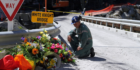 A miner laying down flowers at the White Knight Bridge near the entrance to the Pike River mine. Photo / AP