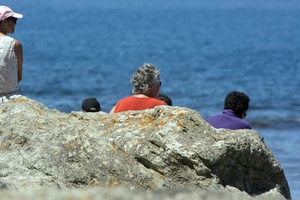 Family members on the rocks at Sandy Bay where searchers worked. Photo / Lynda Feringa