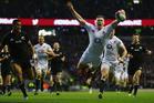 England's Chris Ashton sails through the air as he scores against the All Blacks. Photo / Getty Images