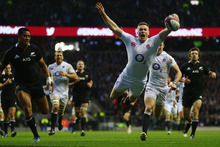 England's Chris Ashton sails through the air as he scores against the All Blacks. Photo / Getty Images
