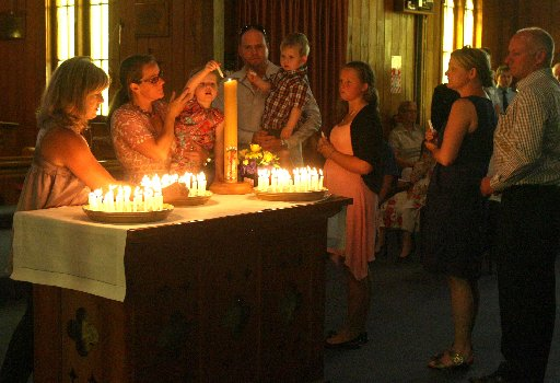 MEMORIAL: Members of the Dean family light memorial candles at St Mark's Church in Carterton yesterday to mark the first anniversary of the hot air balloon crash at nearby Clareville that claimed 11 lives, including that of Des and Ann Dean of Masterton.
