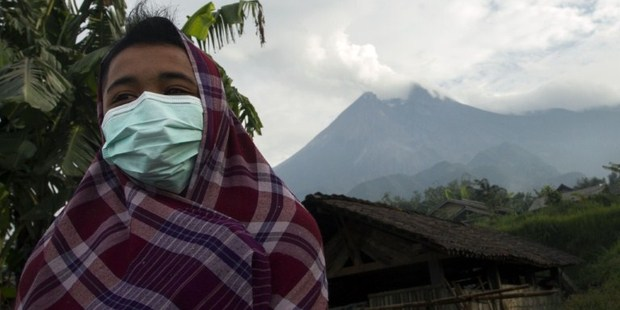 A resident of Cangkringan district in Indonesia's Central Java province wears mask to protect himself against volcanic ash from Mount Merapi (background) after spewing volcanic ash.Photo / AFP