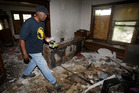 Calvin Brooks searches a house in Cleveland. Photo / AP