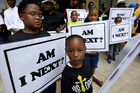 Alvin Duplessis, 10, left, and Thomas McGriff, 5, foreground, hold signs with others from the Watson Memorial Teaching Ministries Church of New Orleans. Photo / AP