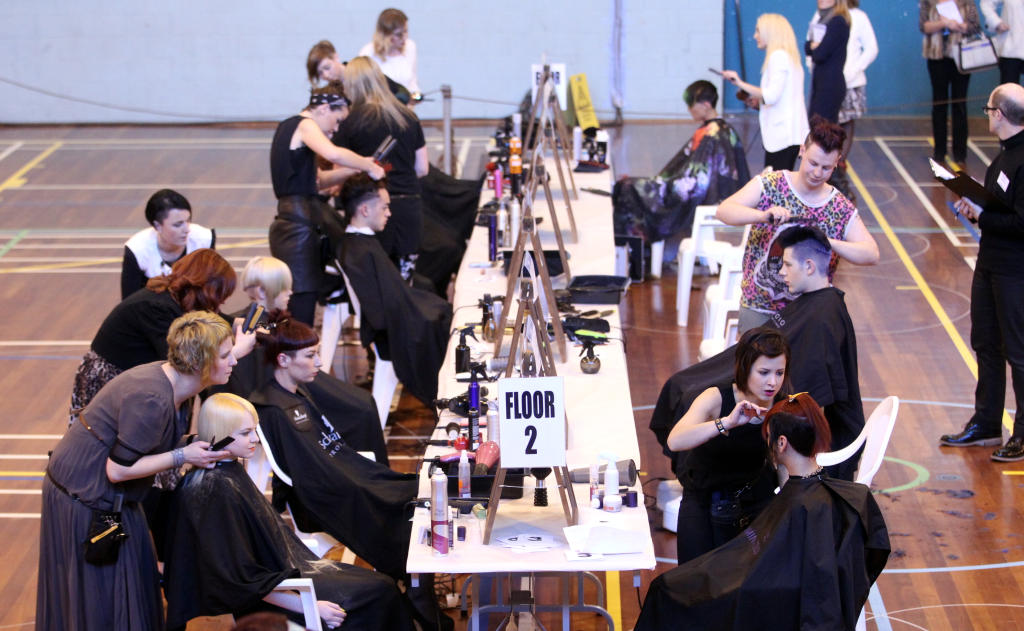 Stylists work on their models as time ticks.