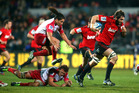 Sam Whitelock of the Crusaders breaks the tackle of Saia Faingaa and Jake Schatz of the Reds. Photo / Getty Images
