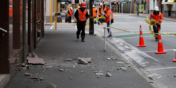 Loading City council workers cleaning up debris from damage as a result of the earthquake in Wellington. Photo / Mark Mitchell