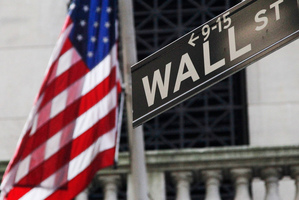 The American flag and a sign for Wall St. Photo / AP