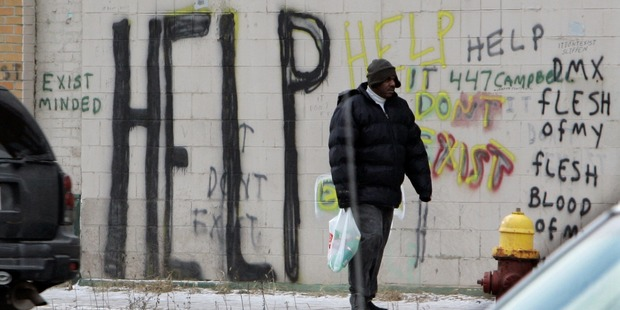 A pedestrian walks by graffiti in downtown Detroit. Photo / AP