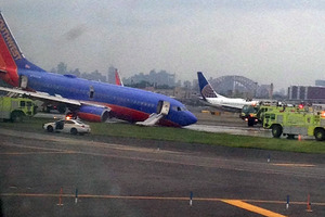 A Southwest Airlines plane whose nose gear collapsed as it touched down on the runway is surrounded by emergency vehicles at LaGuardia Airport in New York. Photo / Jared Rosenstein
