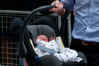 Britain's Prince William carries his son the Prince of Cambridge into a car outside St. Mary's Hospital exclusive Lindo Wing in London. Photo / AP