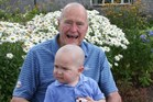 Former US President George H. W. Bush poses on Walker's Point, Kennebunkport, with his head shaved to show support for two year-old Patrick. Photo / AFP