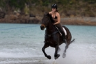 Horse trainer Chloe Phillips-Harris tows wakeboarder Nikita Osborne through the surf at Matauri Bay, Northland. Photo / Brett Phibbs