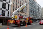 The fire service remove loose metal sheeting from the side of a high rise building in Wellington. Photo / AFP
