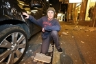 Kyle Woods of Wellington poses with his car which was damaged by falling rubble on Featherston Street.