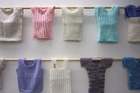 A selection of hand-knitted baby singlets going on display in NZ Parliament in honour of the royal birth.