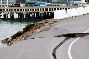 Large cracks are seen in the road near where the land fell into the sea at the Port Wellington Container terminal. Photo / AFP