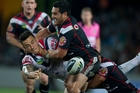 Sonny Bill Williams offloads in the tackle of Warriors Konrad Hurrell and Thomas Leuluai. Photo / Brett Phibbs