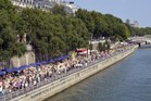 People walk on the Seine river banks on the first day of the 12th edition of Paris-Plage. Photo / AFP
