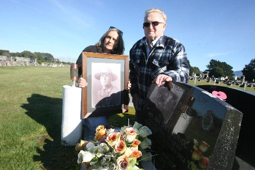 Anzac medal stolen from Percy Pope's grace in Greytown cemetery. Son Les Pope and his daughter Mary Pope holding a photo of Percy at the grave. The missing medal was at far right.