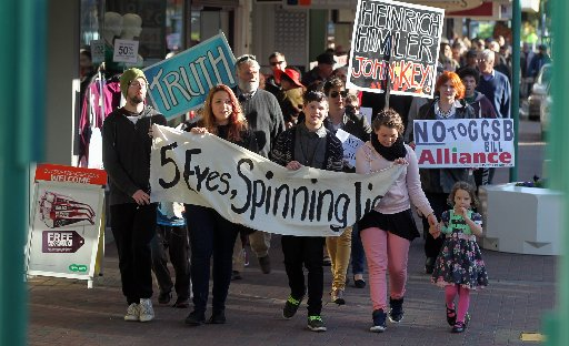"Ben Weir, Jenna Ulyatt, Hayden Calder, Hannah-Brie Reid, friends from Napier, carrying a banner ""5 Eyes, Spinning Lies""."