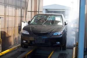 A vehicle is driven through a 'de-con' cleaning machine during the importation process.